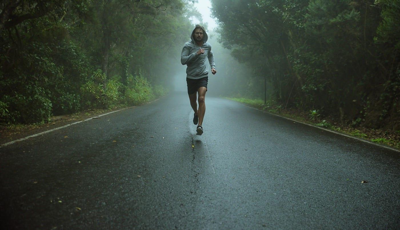 марафонский бегун на темной дороге