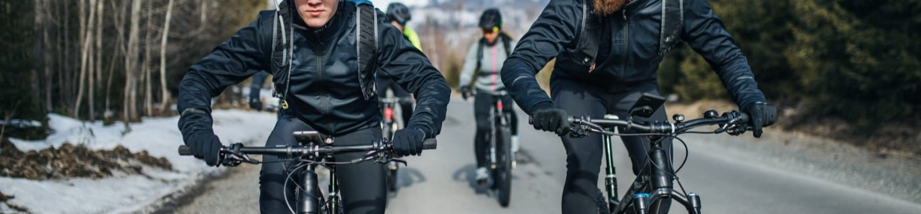 A group of young mountain bikers riding on road outdoors in winter.